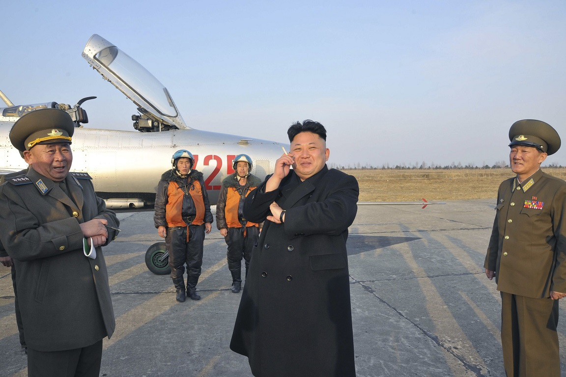 North Korean leader Kim Jong Un (2nd R) smokes a cigarette as he attends a flight exercise of the KPA Air and Anti-Air Force Unit 188